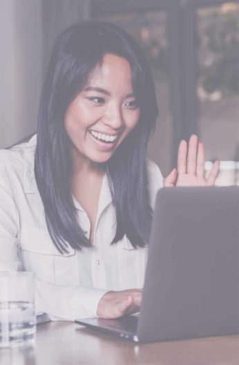A woman smiling and waving at someone she is video chatting with